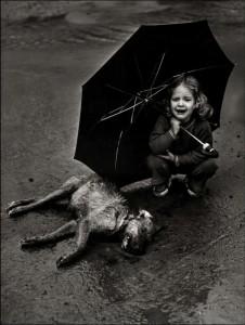 niña bajo un paraguas, llorando junto a un perro muerto en la calle